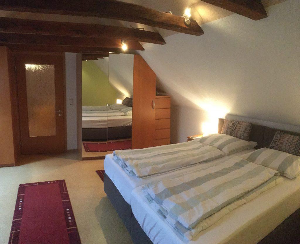 Großes Schlafzimmer mit offenen Dachbalken und Doppelbett